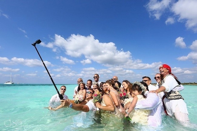 the wedding couple and guests take a selfie in the water